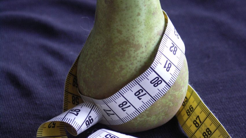 A plus-sized pear wrapped in measuring tap